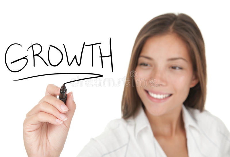 Growth in business. Growth and success in business concept. Young beautiful businesswoman with pen writing growth on whiteboard. Focus on the black marker. Mixed stock photo