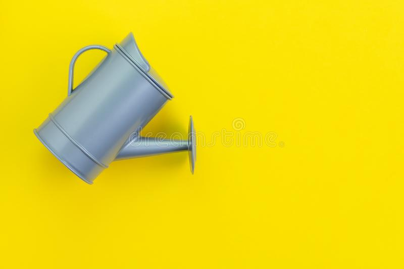 Growth idea, grow or investment profit concept, small gray watering can on yellow background with copy space.  royalty free stock photography