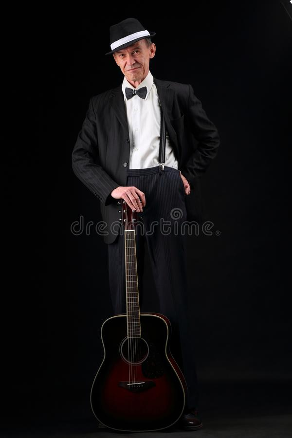 Growth portrait of an elderly musician with a guitar. Full-length portrait of an elderly jazz musician with a guitar in retro style royalty free stock photography