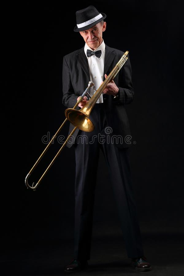 Growth portrait of an elderly musician with a trombone. Full-length portrait of an elderly jazz musician with trombone in retro style stock image