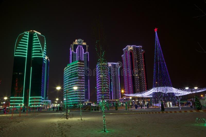 Grozny Grozny complex van wolkenkrabbersstad bij nacht in neonlichten stock fotografie