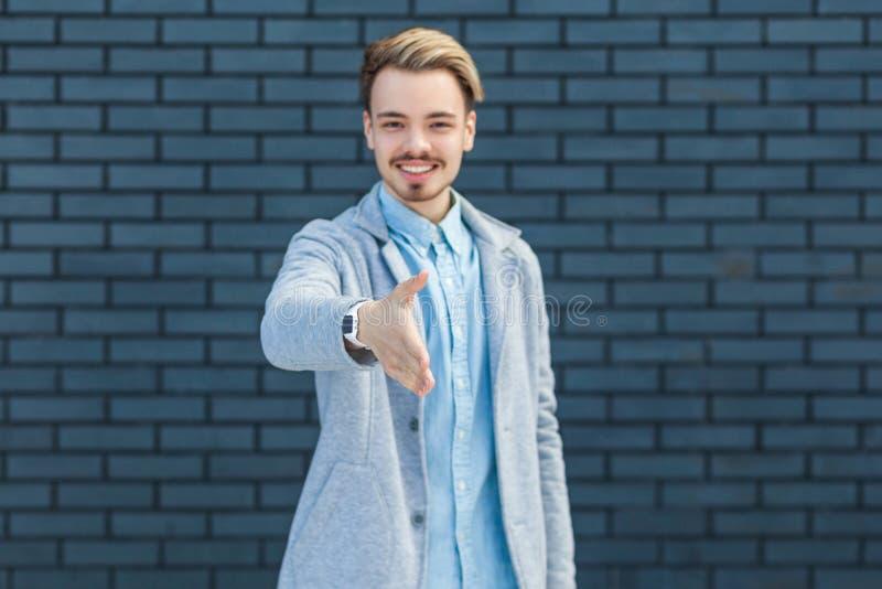 Gruß und hanshake Porträt des glücklichen hübschen jungen blonden Mannes in der Stellung der zufälligen Art, im toothy Lächeln un stockfotos