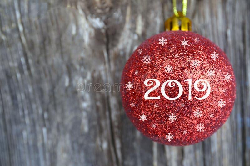 Grußkarte des neuen Jahres 2019 mit rotem Weihnachtsball auf altem hölzernem Hintergrund Festliche Dekoration der Winterurlaube m stockfoto