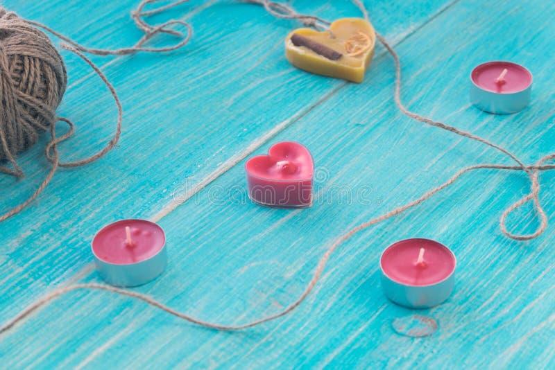 Grußkarte mit blauem hölzernem schäbigem Hintergrund mit Herzen, Kerzen und einem Strang des Threads Flacher selektiver Fokus lizenzfreies stockfoto