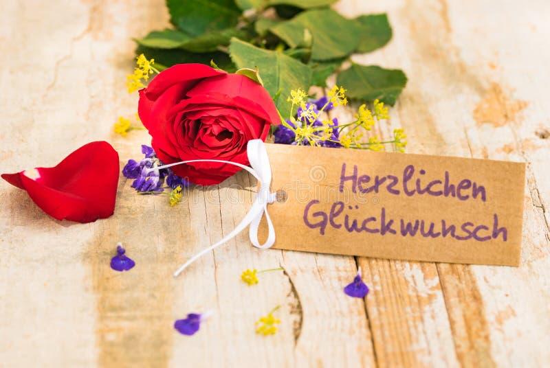 Grußkarte mit deutschem Text, Herzlichen Glueckwunsch, bedeutet Glückwunsch mit romantischer Rotrosenblume lizenzfreie stockbilder