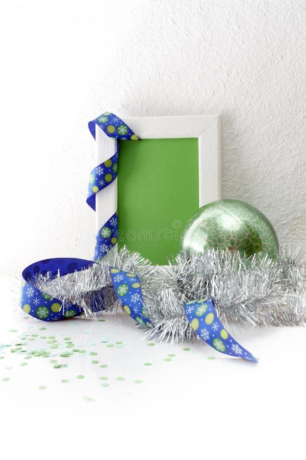 Grußkartenschablone gemacht vom weißen Rahmen und von der Green Card mit blauem Band, grünem Ball, silbernem Lametta und Konfetti stockbild
