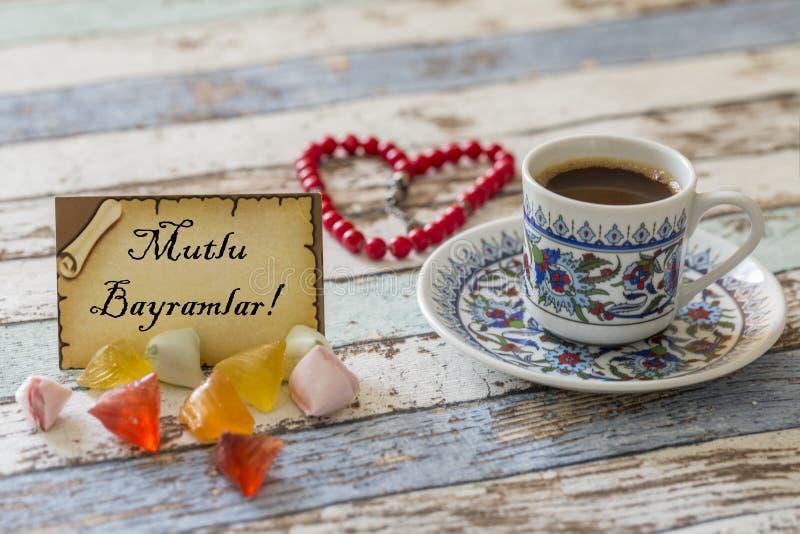 Grußkartenschreiben 'glückliches Eid 'auf Türkisch mit Zuckersüßigkeiten, türkischem Kaffee und geformtem Rosenbeet des Herzens stockbild