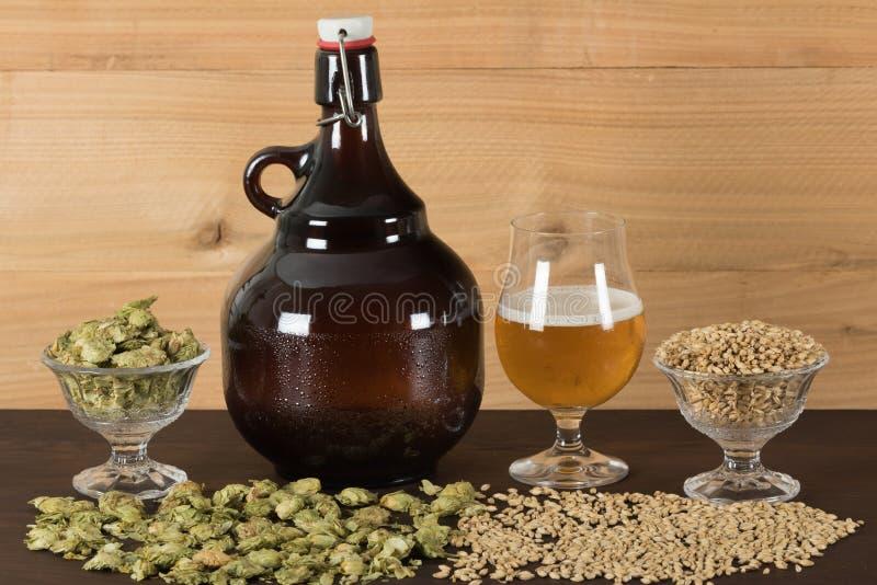 Gruñidor y cubilete de cerveza, con los saltos y las maltas imagen de archivo