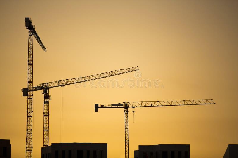 Gru al tramonto. Gru di costruzione e siluette industriali della costruzione sopra il sole ad alba. immagini stock