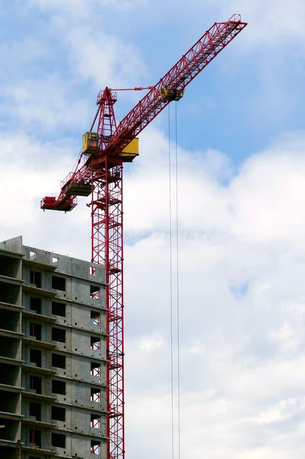 Gru della costruzione contro il und della costruzione e del cielo nuvoloso fotografie stock