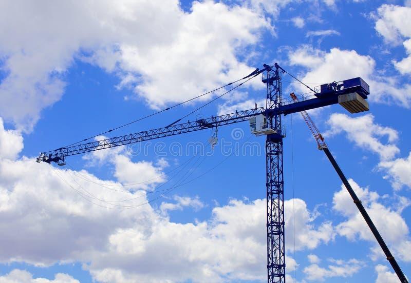 Gru della costruzione di edifici contro cielo blu immagine stock