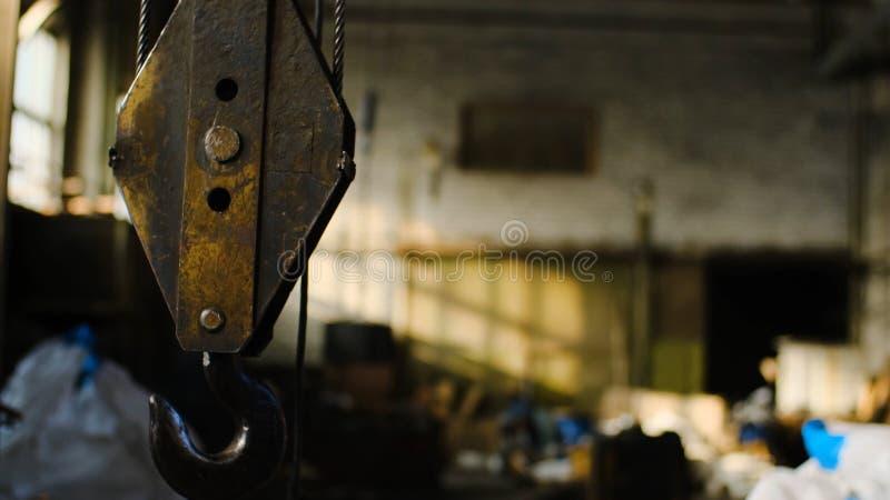 Gru dentro il magazzino Metraggio di riserva Vecchio gancio arrugginito della gru sospeso su fondo del magazzino abbandonato dell immagine stock