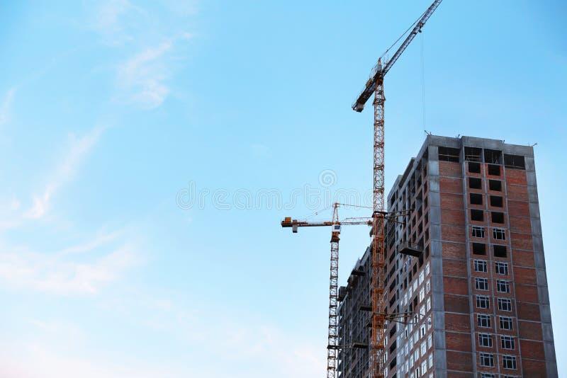 Gru di costruzione e costruzione non finita contro il cielo Spazio per testo fotografia stock