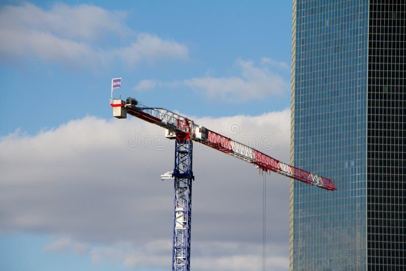 Gru di costruzione e un grattacielo in costruzione contro il cielo blu nel distretto della difesa della La a Parigi immagine stock libera da diritti
