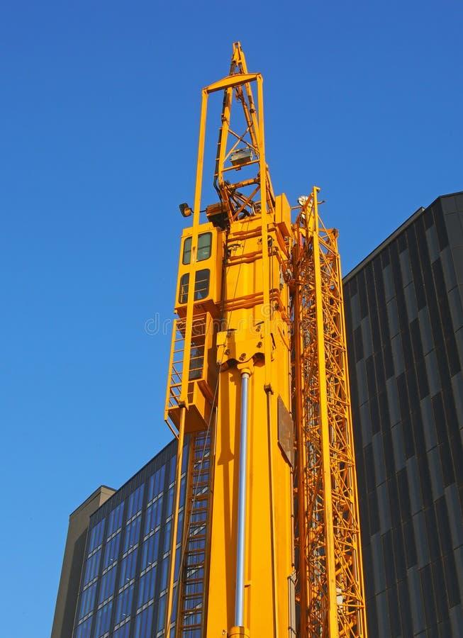 Gru di costruzione gialla piegata con il cavalletto attaccato al lato che aspetta per essere spiegato su un cantiere urbano fotografie stock libere da diritti