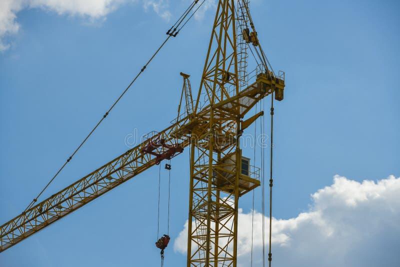 Gru di costruzione di palazzo multipiano con una freccia lunga di colore giallo contro il cielo blu sopra una nuova costruzione m fotografie stock
