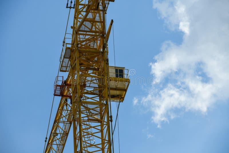 Gru di costruzione di palazzo multipiano con una freccia lunga di colore giallo contro il cielo blu sopra una nuova costruzione m immagini stock