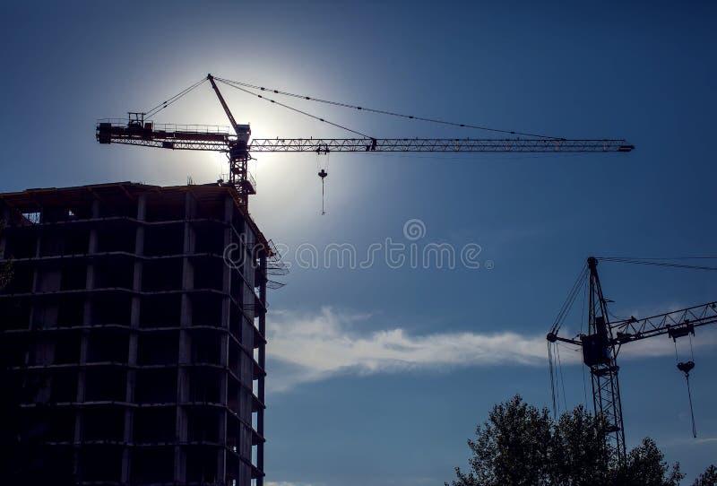 Gru di costruzione su un cantiere contro il backgroun del cielo blu fotografia stock