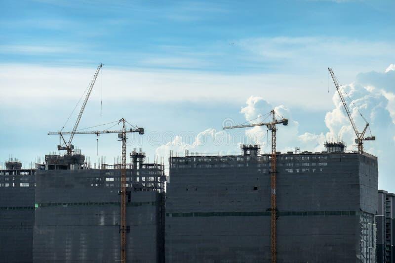 Gru e costruzioni di costruzione in costruzione e cielo nuvoloso immagini stock