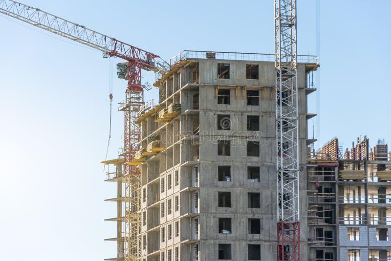 Gru ed edificio residenziale di palazzo multipiano Costruzione del bene immobile fotografia stock