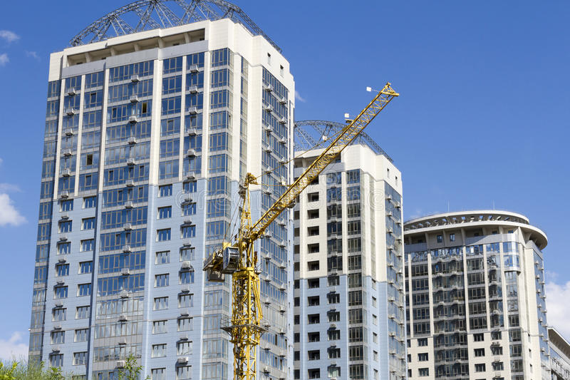 Gru a torre contro lo sfondo di tre nuovi grattacieli immagine stock libera da diritti