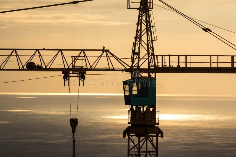 Gru a torre della costruzione che trascura oceano e cielo drammatici all'alba immagini stock