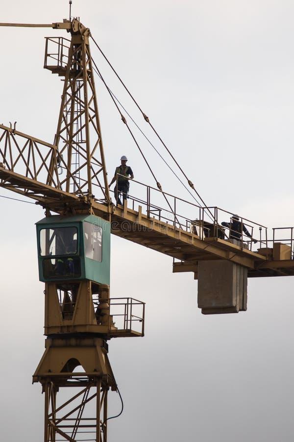 Gru a torre della costruzione con il lavoratore nell'altezza di mostra superiore della gru fotografia stock