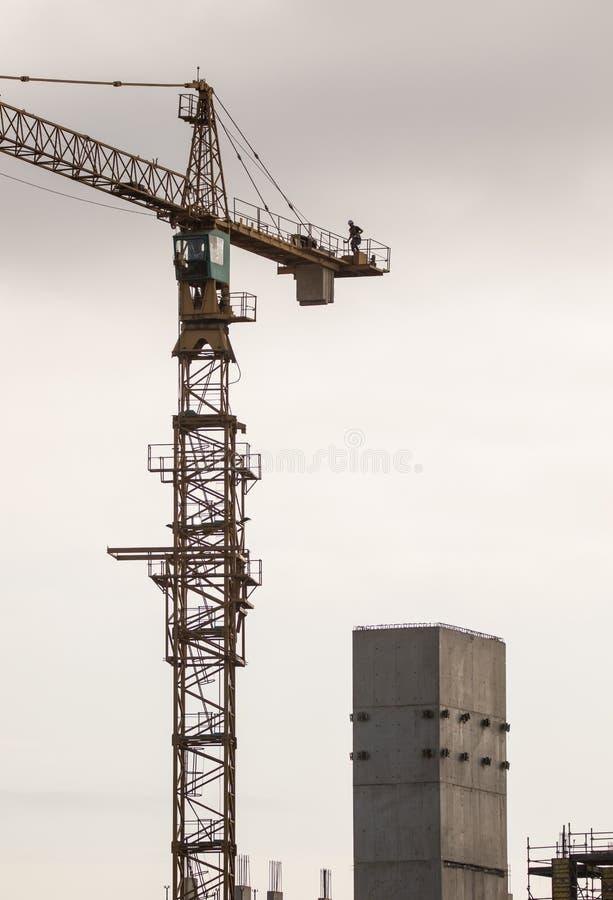 Gru a torre della costruzione con il lavoratore nell'altezza di mostra superiore della gru fotografia stock libera da diritti