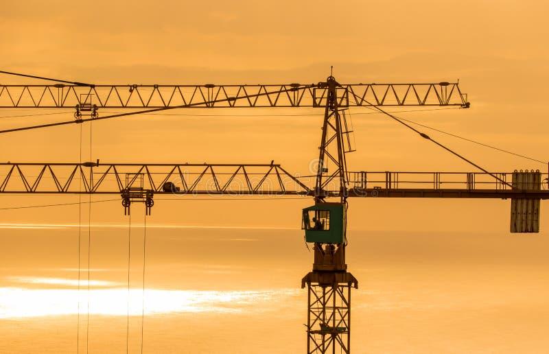 Gru a torre della costruzione contro l'oceano ad alba immagine stock libera da diritti
