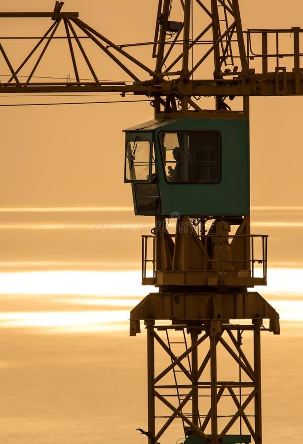 Gru a torre della costruzione contro l'oceano ad alba fotografia stock libera da diritti