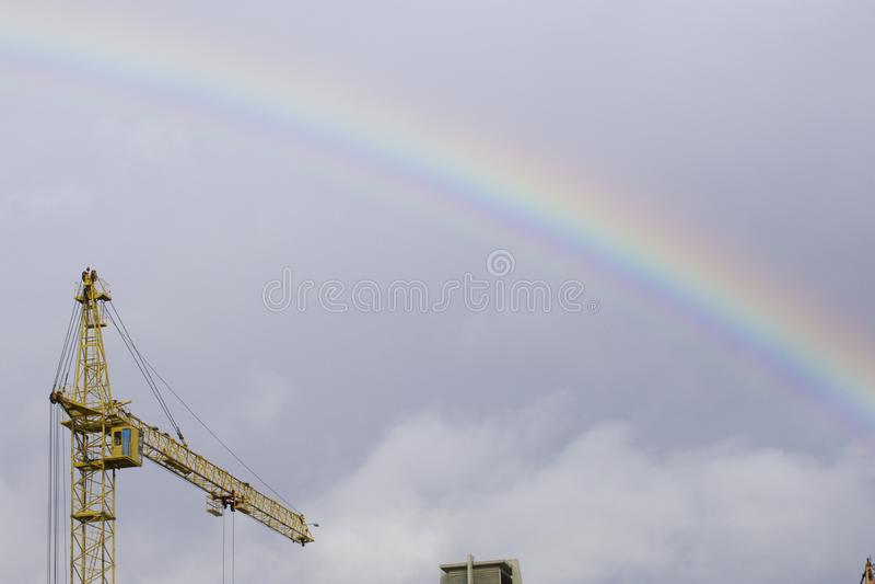Gru a torre gialla contro il cielo blu Sopra lui è un arcobaleno dopo una pioggia fotografie stock libere da diritti
