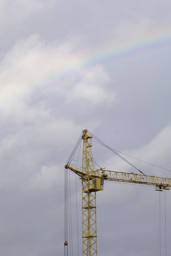 Gru a torre gialla contro il cielo blu Sopra lui è un arcobaleno dopo una pioggia fotografia stock libera da diritti