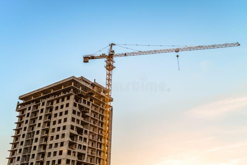 Gru a torre laterale di palazzo multipiano con una costruzione multipiana in costruzione contro il cielo blu fotografia stock
