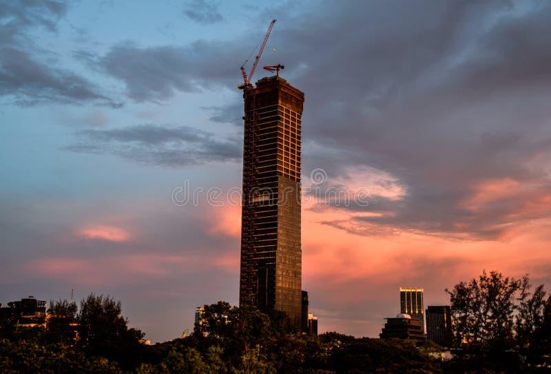 Gru a torre sopra una costruzione non finita nella sera a Bangkok, Tailandia fotografia stock libera da diritti