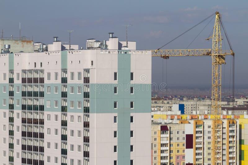 Grua de construção e construção de edifícios residenciais de vários andares imagens de stock