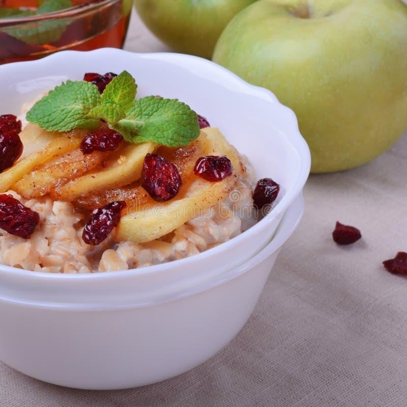 Gruau avec les pommes caramélisées et les canneberges sèches image stock