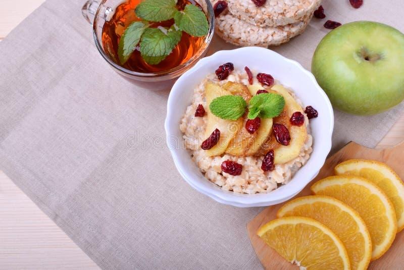 Gruau avec les pommes caramélisées et les canneberges sèches complétées avec la menthe image stock