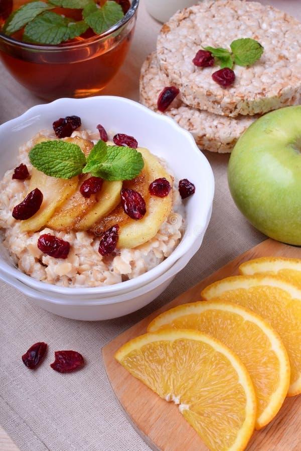 Gruau avec les pommes caramélisées et les canneberges sèches complétées avec la menthe photo stock