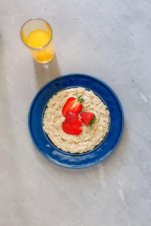 Gruau de farine d'avoine avec les fraises et le verre de jus d'orange photos stock