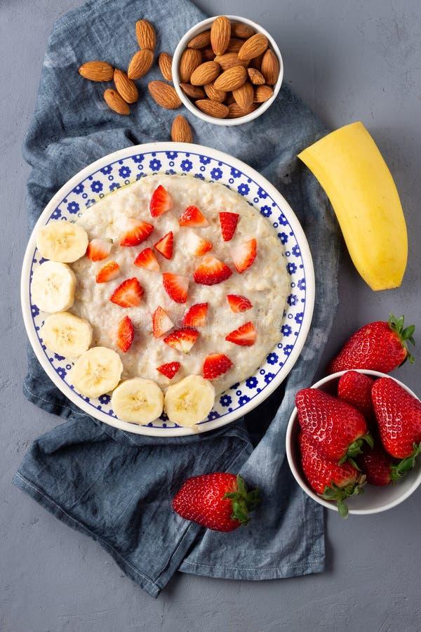 Gruau de farine d'avoine avec les fraises, la banane et les amandes photographie stock