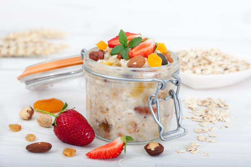 Gruau de farine d'avoine dans le pot en verre avec les fraises, les écrous et les fruits secs frais images stock