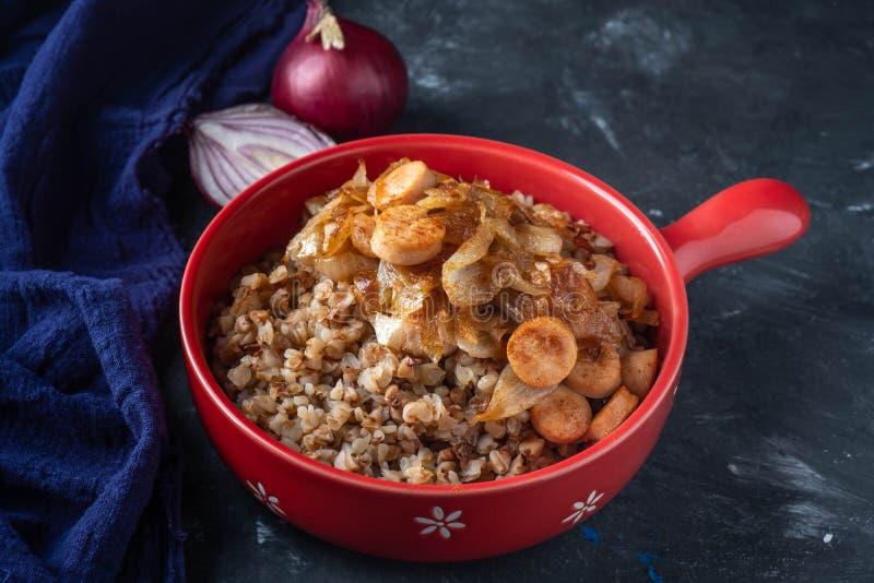 Gruau de sarrasin avec des saucisses et des oignons frits dans une casserole rouge sur un fond foncé, l'espace de copie image libre de droits