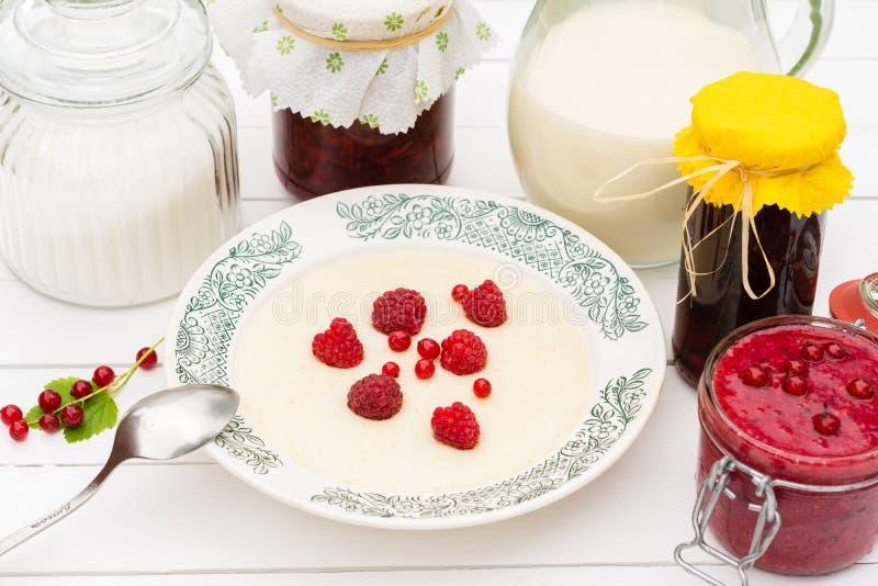 Gruau de semoule avec les framboises, le pot avec du lait et la confiture pour le petit déjeuner photographie stock