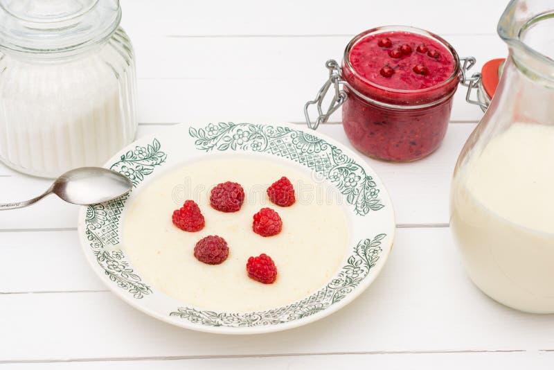 Gruau de semoule avec les framboises, le pot avec du lait et la confiture pour le petit déjeuner photos libres de droits