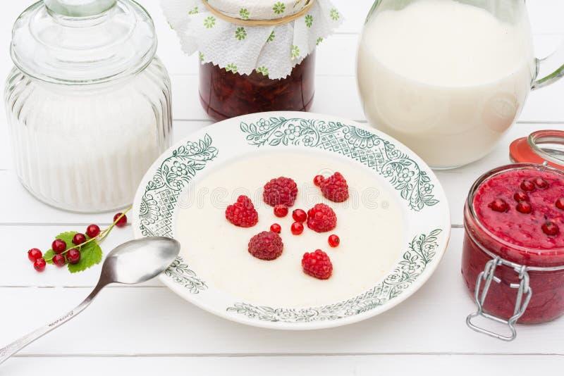 Gruau de semoule avec les framboises, le pot avec du lait et la confiture pour le petit déjeuner photo libre de droits