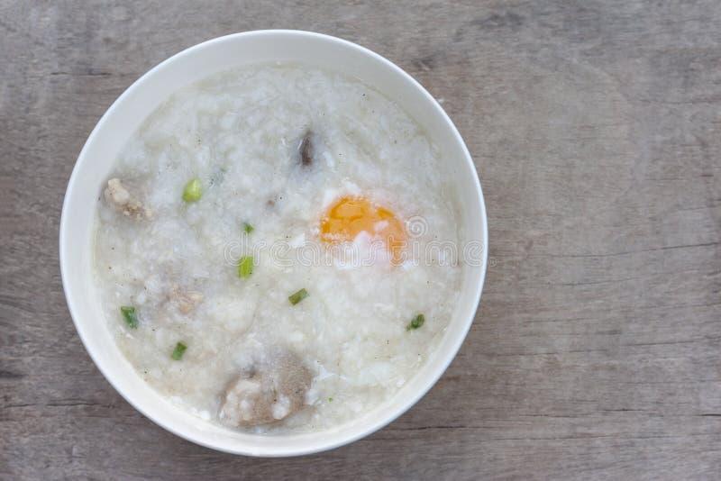 Gruau ou congee de riz avec l'oeuf dans la cuvette blanche sur la table en bois de cru image libre de droits