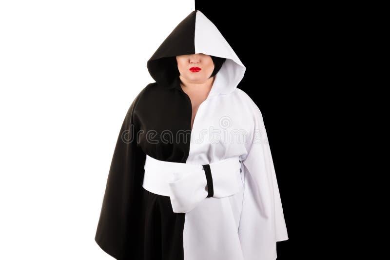 Gruba kobieta z kapiszonem w pięknej czarny i biały sukni na czarny i biały tle zdjęcie royalty free