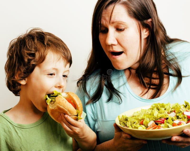 Gruba kobiety mienia sałatka i mała śliczna chłopiec z hamburgeru dokuczać fotografia stock