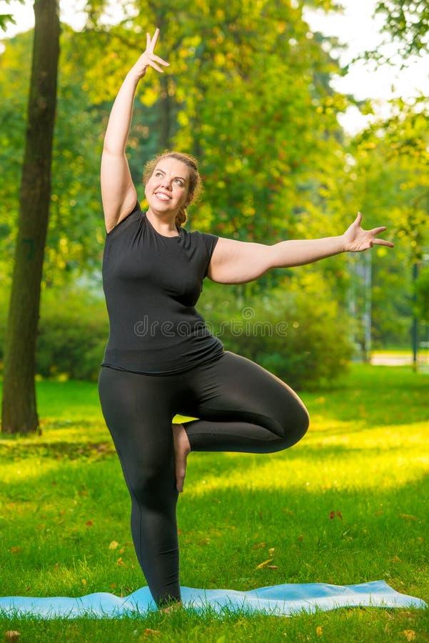 gruba rozochocona kobieta robi joga w parku obrazy royalty free