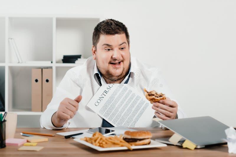 grubi biznesmena łasowania hamburgery i francuzów dłoniaki zdjęcia stock